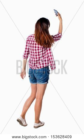 back view of standing young beautiful  girl with tablet computer in the hands of. girl  watching. backside view of person.  Isolated over white background. Girl in shorts doing selfie.