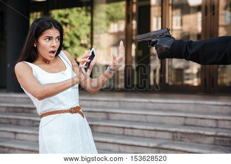 Shocked young woman with mobile phone standing and being threatened by man thief with gun