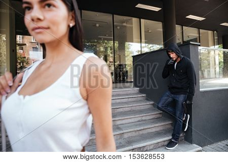 Criminal young man with gun smoking and looking for victim on the street