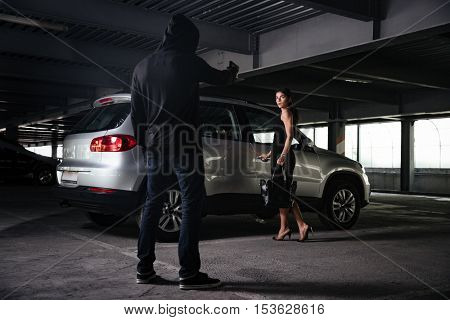 Man thief in black hoodie standing and threatening with gun to young woman on car parking