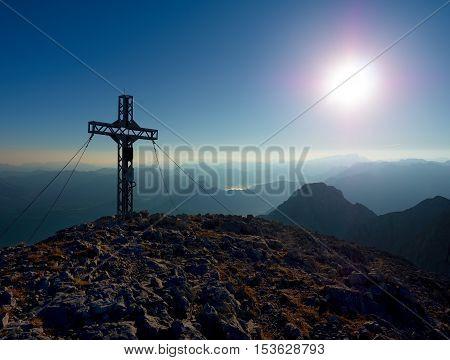 Steel Crucifix At Mountain Peak In Alps. Sharp Rocky Summit, Daybreak Sun In Sky.