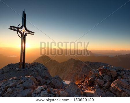 Cross Raised  At Mountain Summit  In Alps. Sharp Peak, Daybreak Sun