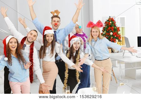 Young people celebrating Christmas at corporate party in office