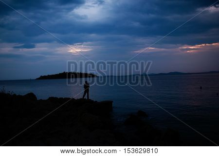 Dark silhouettes of fisherman fishing on coast and island after sunset in sea under cloudy sky on tranquil evening seascape