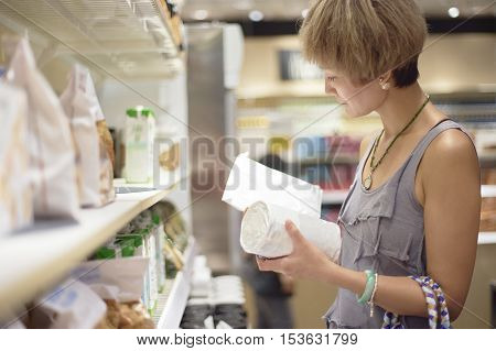 Woman Checking Info On Package In Supermarket