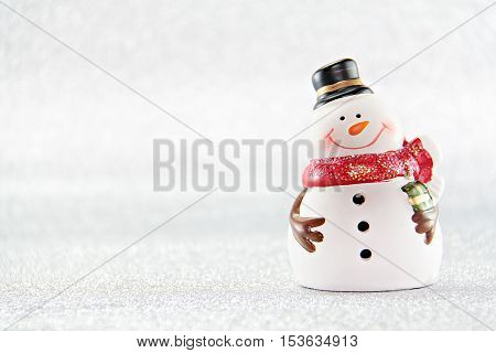 Merry Christmas or Happy New Year concept : Cute snowman doll on silver glitter paper background