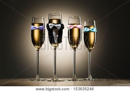 Glasses of champagne dressed in wedding suit and bow tie