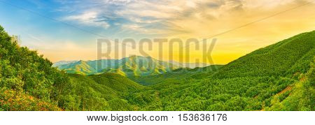 Panoramic view of a mountain valley at sunset time. Panorama