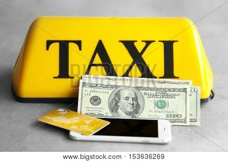 Yellow taxi roof sign with phone, credit card and American dollars on gray background, closeup