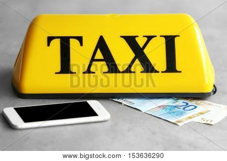 Yellow taxi roof sign with phone and Euro banknotes on gray background, closeup