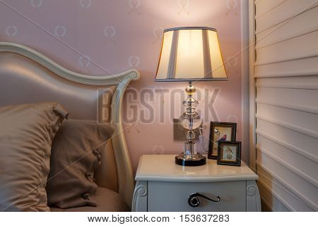 elegant lamp on table near comfortable bed