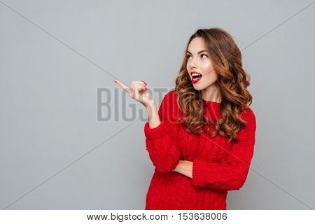 Thoughtful woman in red sweater looking away questioningly looking away