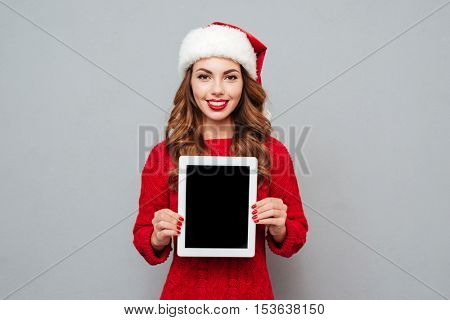 Cheerful pretty young woman in santa claus hat holding blank screen tablet over gray background