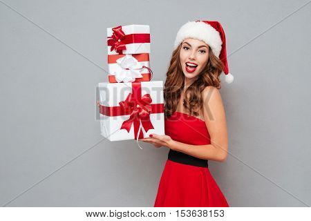 Girl with three christmas gifts. Santa's helper. Dress and Santa's hat