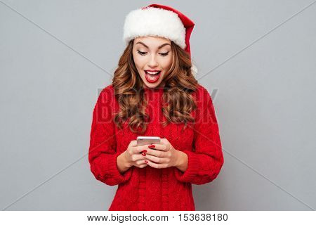 Amazed attractive young woman in santa claus hat using cell phone over gray background