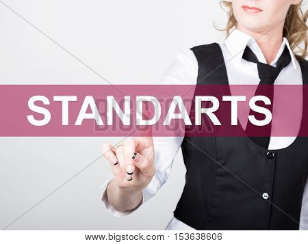 standarts written on virtual screen. technology, internet and networking concept. woman in a black business shirt presses button on virtual screens.
