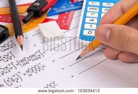 Math Quadratic Equation With Hand Holding Pencil. School Supplies Used In Math. Math Drawing Tools W