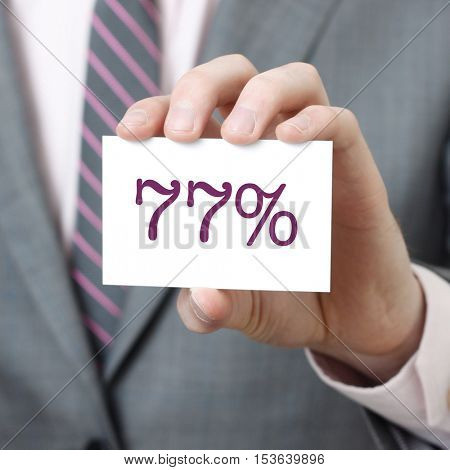77% written on a card held by a businessman