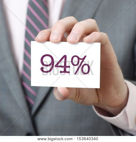 94% written on a card held by a businessman