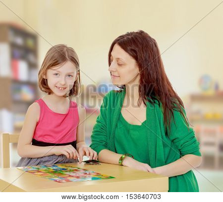 Clever little girl and her teacher at the table laid out cards with pictures.In the children's room where there are shelves with toys.