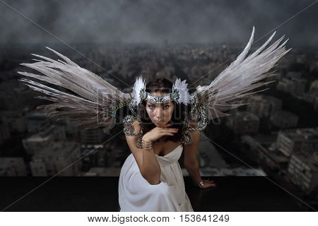Young woman in white dress with angel wings on the background of the smoggy city