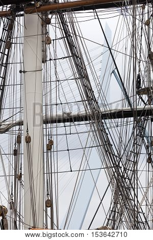 Rigging of a historical sailing ship with the Rotterdam Erasmus bridge in the background