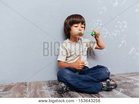 Full length of cute little boy sitting and blowing soap bubbles over gray background
