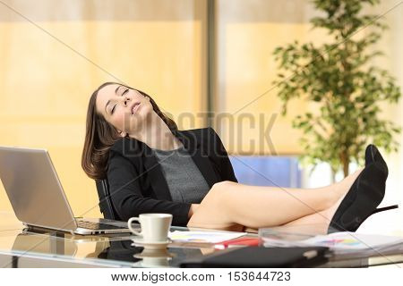 Lazy or tired businesswoman sleeping at work with the legs over the table at office