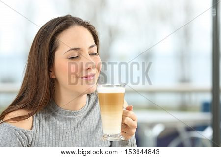 Woman enjoying smelling and holding a macchiato coffee in a restaurant with a window with the sea outdoors in the background