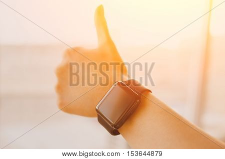 Close up of smartwatch on young woman's wrist showing thumbs up gesture with sunlight effect