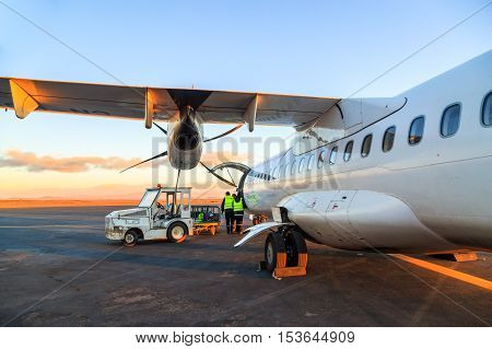 Loading Luggage In Airplane At Daybreak