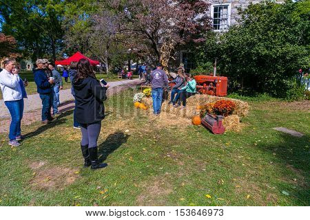 Lancaster PA USA - October 9 2016: Visitors pose with an old tractor at the Landis Valley Farm and Museum during the annual Harvest Day event.