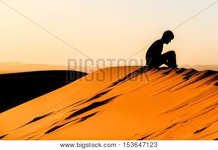 Meditating Young Man Sitting On Top Of A Dune Of Sahara