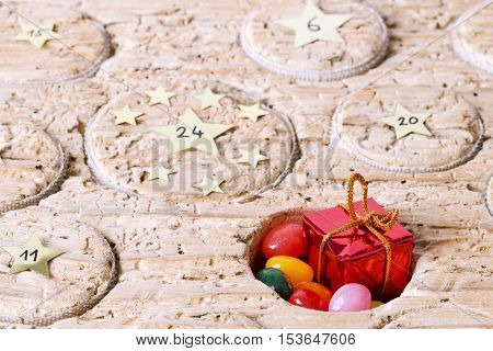 Open window of Advent calendar handmade from old timber. Circular space filled with a small gift and jelly beans. Calendar to count the days before Christmas. Medieval wood with wormholes. Macro photo