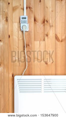 Working white electric convector heater plugged to timer power socket operated in smart house system against wooden wall inside room vertical front view closeup