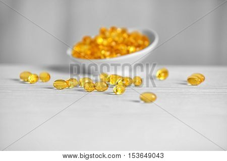 Cod liver oil capsules on white wooden table