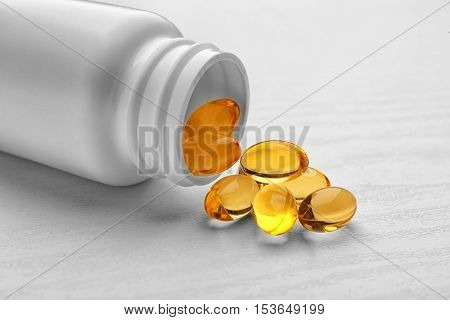 Medicine bottle and cod liver oil capsules on white wooden background