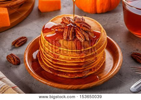 Stack of homemade pumpkin pancakes with pecans and maple syrup selective focus.