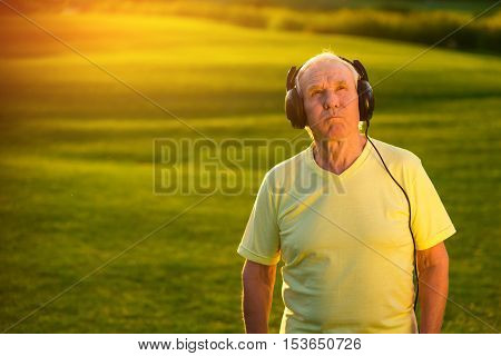 Elderly man in headphones. Person with serious face outdoor. Good music doesn't get old. Best rock ballads.