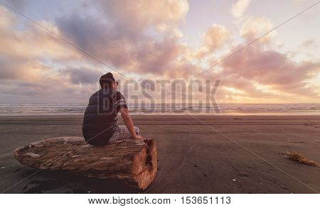 Man sitting on log at beach and enjoying sunset.