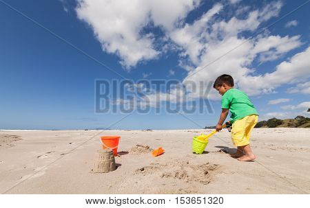 Kid making sandcastle at pakiri beach, Auckland.