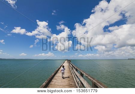 A kid running on wharf heading towards fishing dock.