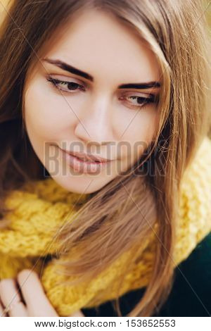 Pretty woman in a yellow knit scarf, close-up.