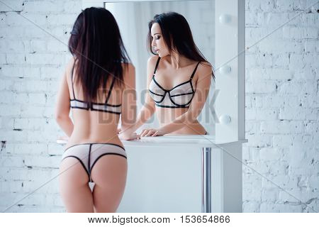 Perfect, sexy body and ass of young woman wearing seductive lingerie. Beautiful hot female in lacy underware posing close to mirror.