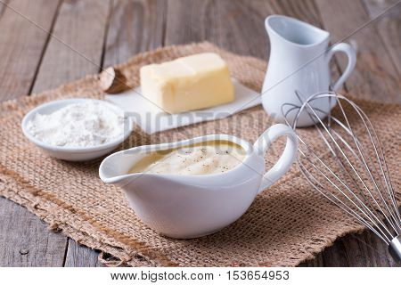 Bechamel sauce on kitchen table on a wooden background