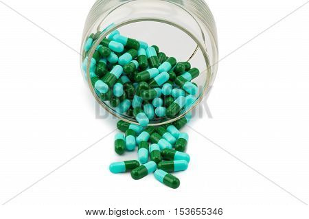 Antibiotic capsule spilling out of a glass bottle on white background