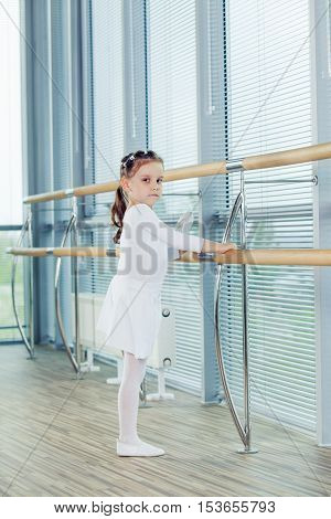 Little ballerina girl. Adorable child dancing classical ballet in a white studio. Children dance. Kids performing. Young gifted dancer in a class. Preschool kid taking art lessons.