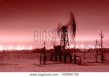 Working oil pump jack at night time. Oilfield during winter. Refinery lights background. Oil and gas concept. Toned.