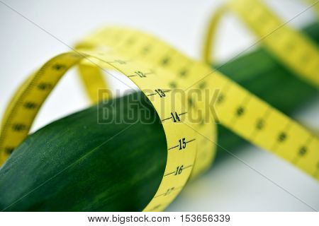 closeup of a measuring tape around a cucumber depicting the male member