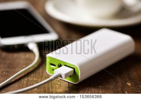 closeup of a powerbank charging a smartphone placed on a wooden table next to a cup of coffee